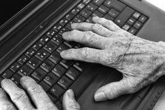 Elderly hands on keyboard of laptop. Royalty Free Stock Image