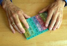 Elderly hands with pill container. Close-up of hands of elderly man holding pill container Royalty Free Stock Image