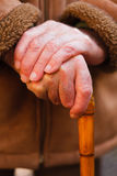 Elderly hands resting on walking stick. An elderly man standing, leaning on a wooden walking stick Stock Images