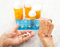 Elderly Hands Sorting Pills. Closeup view of an eighty year old senior woman's hands as she sorts her prescription medicine Stock Photography