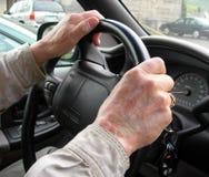 Elderly hands on steering wheel. Hands of elderly man on steering wheel as he drives through traffic Royalty Free Stock Image