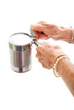 Elderly Hands Struggle with Can Opener. Closeup of elderly hands, with arthritis, struggling to use a can opener. Isolated on white stock images