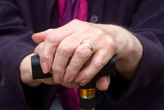 Elderly hands on walking stick. Close up of elderly womans hand resting on her walking stick Stock Photo