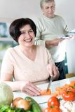 Elderly happy couple cooking. At kitchen stock images