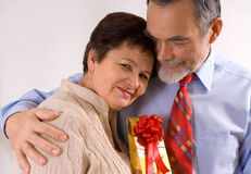 Elderly happy couple with gift Royalty Free Stock Photography