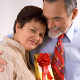 Elderly happy couple with gift. Smiling and embracing royalty free stock images