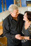 Elderly happy couple at home. Elderly happy attractive smiling couple embracing at home Stock Photography