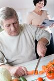 Elderly happy couple at kitchen. Elderly happy couple cooking at kitchen. Focus on man Stock Photography
