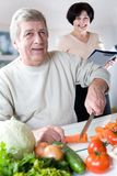 Elderly happy couple at kitchen. Elderly happy couple cooking at kitchen. Focus on man royalty free stock images