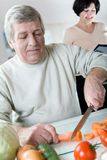 Elderly happy couple at kitchen. Elderly happy couple cooking at kitchen. Focus on man Stock Image