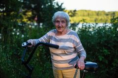 An elderly happy woman with a Bicycle in the Park. stock photography
