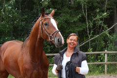 Elderly happy woman and brown horse in the forest. Happy smilling elderly woman and brown horse portrait in the forest Royalty Free Stock Photos