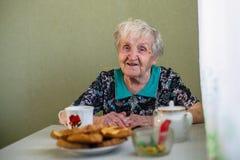 Elderly happy woman drinking tea in the kitchen. stock photos