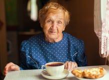 Elderly happy woman drinking tea. Royalty Free Stock Photo