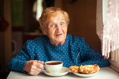 Elderly happy woman drinking tea sitting in the kitchen. Stock Photo