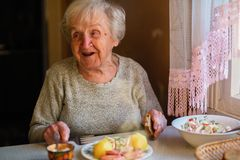 Elderly happy woman eat sitting at dinner table at home. stock photos
