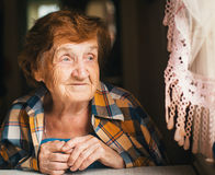 An elderly happy woman is looking out the window. Royalty Free Stock Photography