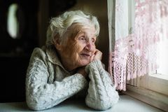Elderly happy woman looks out the window. royalty free stock image