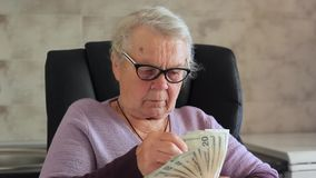 Elderly happy woman with pack of money/ Dollars in the hands of an old woman