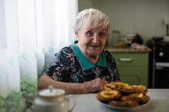 Elderly happy woman sitting in the kitchen. stock photography
