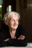 An elderly happy  woman sitting at the table. Stock Photos