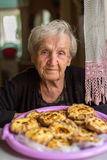 An elderly happy woman sitting at the table with the cakes. Royalty Free Stock Photography