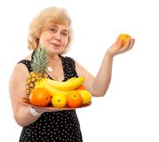 Elderly happy woman treat fresh fruits royalty free stock photo