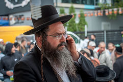 An elderly Hasid in traditional Jewish hat talking on the phone Stock Images