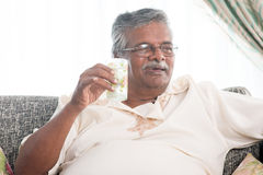 Elderly healthcare. Concept. Old Indian man drinking a glass water, sitting on sofa at home. Retired senior people living lifestyle Royalty Free Stock Photo