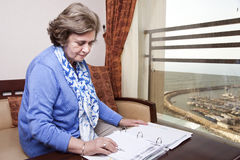 Senior Businesswoman about to Write. An elderly (in her late 60's) business woman sitting in a hotel's business lounge, looking down at an empty page in a Royalty Free Stock Images