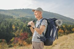 Elderly hiker holding a pair of binoculars outdoors Royalty Free Stock Photos