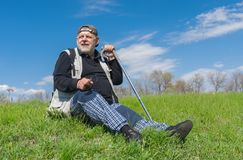 Elderly hiker sitting on green hill Royalty Free Stock Image