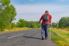 Elderly hiker walking on a roadside in Ukrainian rural area Royalty Free Stock Images