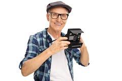 Elderly hipster holding a polaroid camera. Isolated on white background Stock Photos