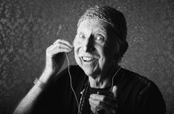 Elderly Hiptser Listening to Handheld Audio Device Royalty Free Stock Images