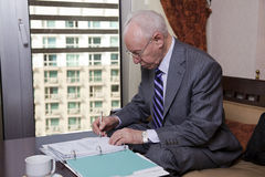 Senior Businessman Writing Notes. An elderly (in his 80's) business man wearing suit and tie sitting in a hotel's business lounge, going over some papers and Royalty Free Stock Image