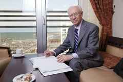 Glacier Cliff. An elderly (in his 80's) business man wearing suit and tie sitting in a hotel's business lounge, looking at camera with a slight smile on his face Royalty Free Stock Photography