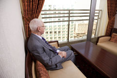 Senior Businessman Looking Out the Window. An elderly (in his 80's) business man wearing suit and tie sitting in a hotel's business lounge, looking through the Royalty Free Stock Images