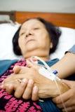 Elderly holding hands in sickness stock images