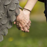 Elderly holding a young hand, close-up hands. Stock Images