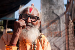 Elderly holy man with vintage glasses. Elderly holy man sadhu with vintage glasses poses outdoor in Orchha, Madhya Pradesh, India. Orchha had a population of Royalty Free Stock Photos