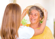 Elderly home care. Caregiver put the hat on the happy elderly womans head royalty free stock photo