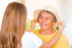 Elderly home care. Caregiver put the hat on the happy elderly womans head royalty free stock photography