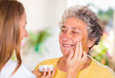 Elderly home care. Caregiver rubs the face cream on the elderly womans face royalty free stock image