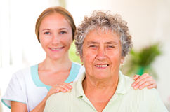Elderly home care. Happy elderly women with her caregiver in the background stock image