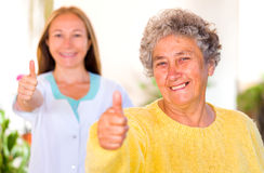 Elderly home care. Happy elderly women with her caregiver showing thumbs up stock image