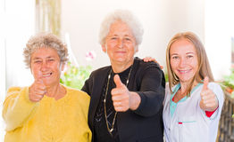 Elderly home care. Happy elderly women with their carer showing thumbs up royalty free stock photos