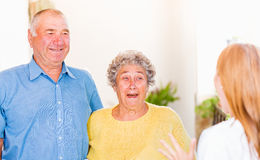 Elderly home care. Photo of elderly couple surprised by their daughter stock photography