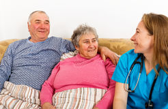 Elderly home care. Photo of elderly couple and young female doctor stock images
