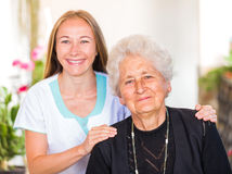 Elderly home care. Photo of happy elderly women with her caregiver royalty free stock photography